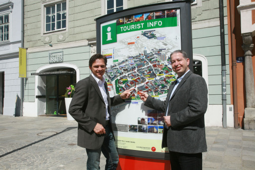 Stadtmarketingdirektor Peter Jungreithmair und Tourismusverband-Obmann Helmut Platzer präsentieren die erste Gästeinformationstafel am Welser Stadtplatz