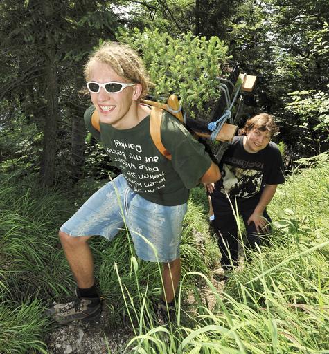 Mit schwer beladener Holz-Krax'n geht Christoph (18) aus Bad Goisern mit Judith (39) aus Wien hinauf zum Einsatzort.