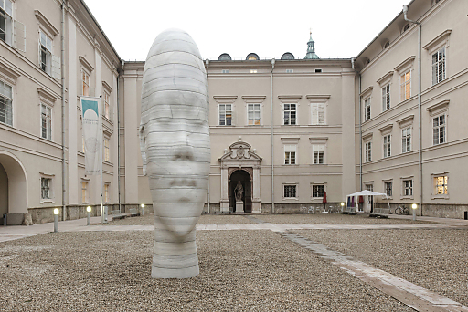 """Der katalanische Künstler Jaume Plensa hat für den """"Walk of Modern Art"""" in der Salzburger Altstadt eine Skulptur aus weißem spanischem Marmor geschaffen. Seit dem 9. Oktober 2010 ziert ein fünf Meter hoher Mädchenkopf die """"Dietrichsruh"""" der Universität Salzburg."""