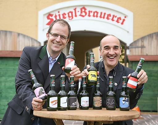 """Christopher Losmann (Stiegl) und Prof. Antonino Benincasa (Freie Universität Bozen) freuen sich über die frech, extrem gefühlvoll, heimatverbunden und orginell gestalteten Etiketten der Braukunst-Edition """"Südtirol""""."""