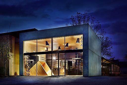 Wie ein gigantisches Tor aus Glas und grünem Beton empfängt der Neubau des Heurigenweinguts Frühwirth in Teesdorf die Besucher