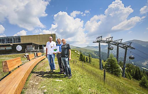 """Die beiden Vorstände der Bad Kleinkirchheimer Bergbahnen Hansjörg Pflauder (links) und Rudolf Egger (rechts) mit Arnold Oberacher (Mitte), ConOs-Tourismusberatung, während der Zertifizierung als eine der """"Besten Österreichischen Sommer-Bergbahnen"""" bei der Bergstation der Nationalparkbahn Brunnach (1.902 m) direkt am Biosphärenpark Nockberge mit einer der 10 Meter langen """"nock/art""""-Bänke"""