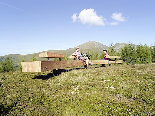 """Eine der neuen 10 Meter langen, monumentalen """"nock/art""""-Bänke, die an verschiedenen markanten Punkten am Berg und im Tal aufgestellt wurden. Im Bild: die Bank in der Nähe der Nationalparkbahn Brunnach-Bergstation"""