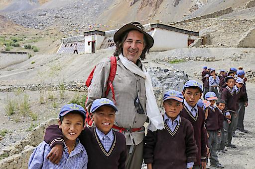 """Weltweitwandern-Gründer Christian Hlade mit Kindern aus dem nordindischen Dorf Lingshed vor der von ihm erbauten """"Solarschule""""."""