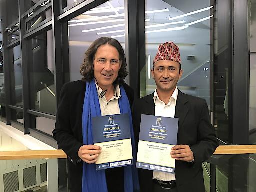 Weltweitwandern-Gründer Christian Hlade und langjähriger Nepal-Partner Sudama Karki halten stolz die TRIGOS-Nominierung für die 'Beste Partnerschaft international' in Händen