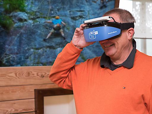 Mag. Wolfgang Kleemann, Generaldirektor der Österreichischen Hotel- und Tourismusbank (ÖHT) testet bei seinem Besuch im Tourismusbüro Sattendorf die neuen VR-Brillen zur Gästeinformation