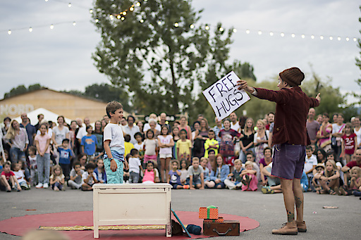 Besucher des Theaterspektakels verfolgen die Vorführung eines Strassenkünstlers auf der Landiwiese in Zürich.