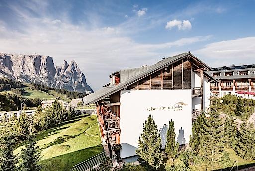Das Hotel Seiser Alm – Urthaler liegt auf der höchsten Alm Europas. Von der Terrasse aus fällt der Blick direkt auf die schroffen Felsen der Dolomiten.