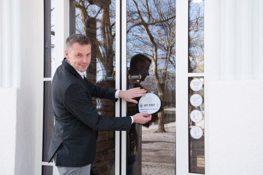 Villa Lido Chef Franz Huditz befestigt das Safe Service Emblem am Restaurant.