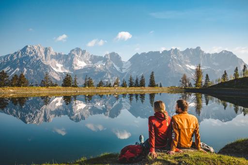 Zwei Menschen sitzen mit Blick auf den Wilden Kaiser am Astbergsee in Going.