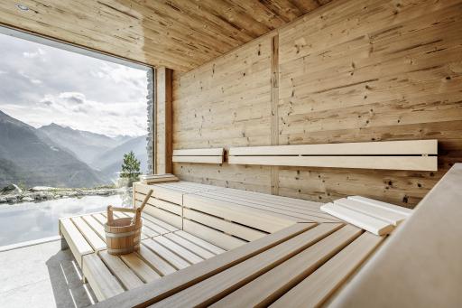 Das Sanarium® von KLAFS im Altholzstil im neuen Leni Mountain Chalet kombiniert ein klassisches Saunabad, ein Soft-Dampfbad, ein Aromabad und ein Warmluftbad. Die raumhohen Fenster holen die traumhaften Berge in den Raum.