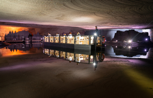 Besucher gleiten mit einem Guide und Floß über den unterirdischen Salzsee