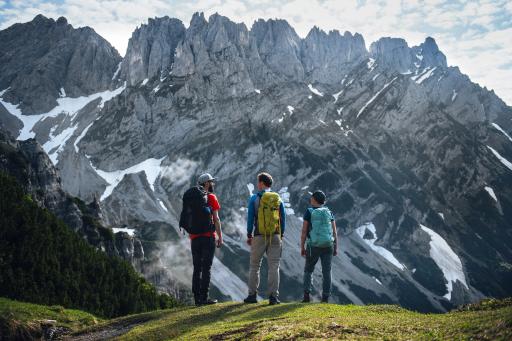 Alleine reisen – gemeinsam wandern: Eine Gruppe von drei Personen vor der Kulisse des Wilden Kaisers.